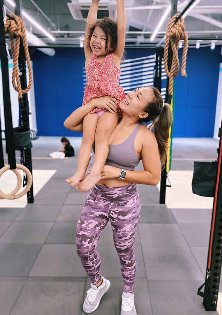 fit mom poses with child